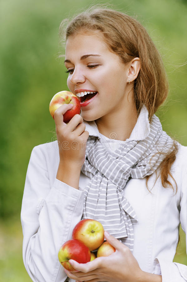 Smiling Cute Woman Bites Ripe Apple Royalty Free Stock Images
