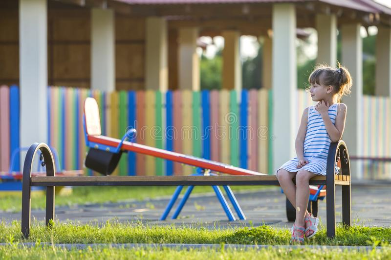 Smiling cute young girl sitting alone outdoors on bench on sunny summer day stock photography