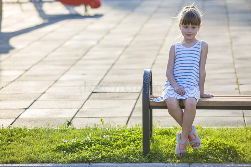 Smiling cute young girl sitting alone outdoors on bench on sunny summer day royalty free stock images
