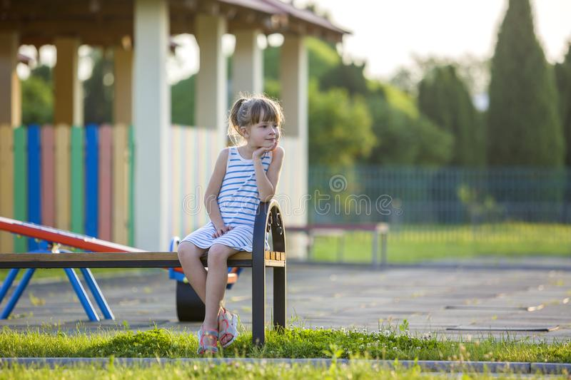 Smiling cute young girl sitting alone outdoors on bench on sunny summer day royalty free stock photography