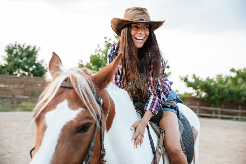 Smiling cute young womna cowgirl riding a horse outdoors. And laughing stock image