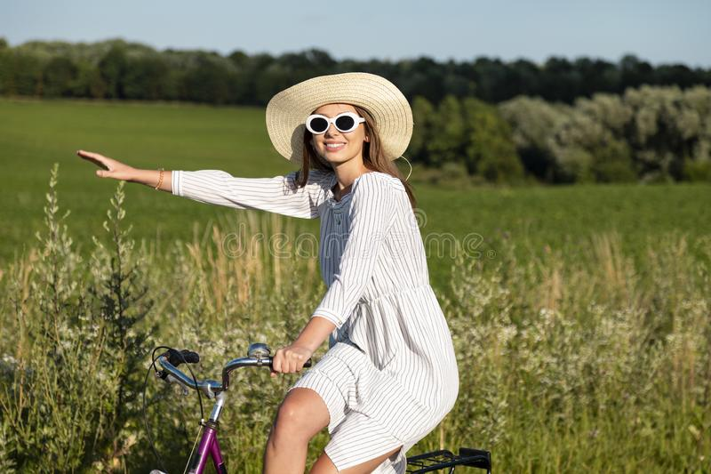 Smiling Cycling Girl in Sunglasses Posing. Smiling cycling girl in sunglasses and straw hat posing pointing aside with her hand stock photos