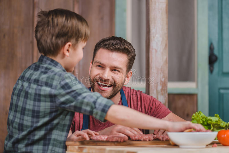 Smiling dad and son cooking meat burgers together royalty free stock photos