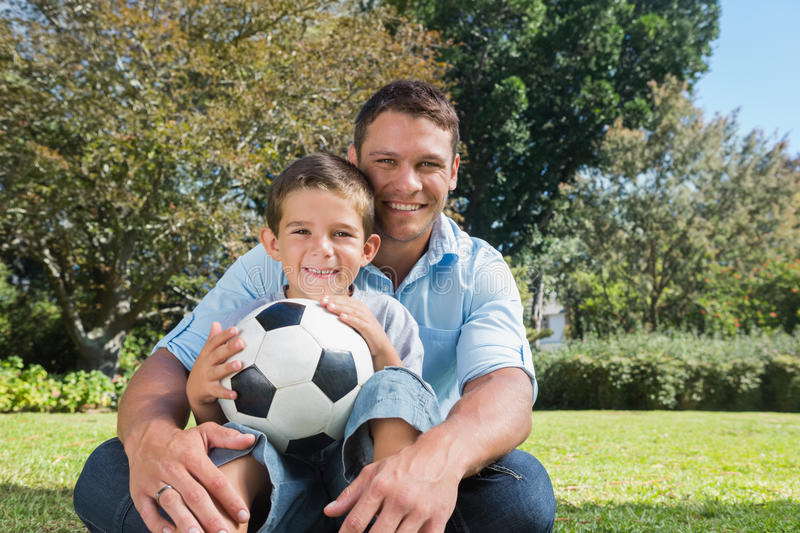 Smiling dad and son in a park. Smiling dad and son with a football in the park on sunny day stock images