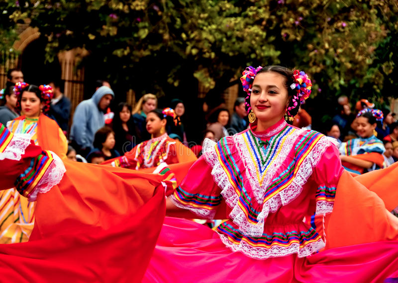 Smiling dancer in bright-colored dress in parade stock photo