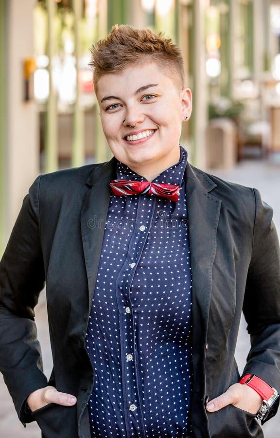 Smiling Dapper Gender Fluid Young Woman. Smiling dapper young gender fluid woman on city sidewalk stock photos