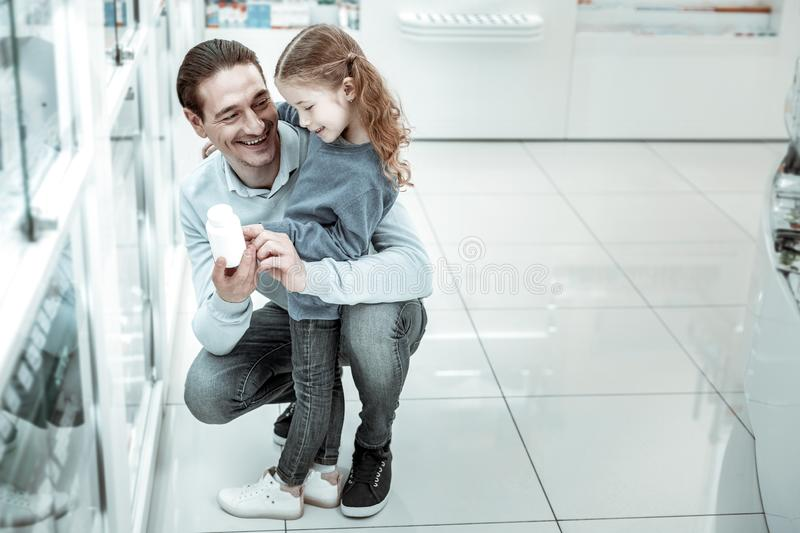 Smiling dark-haired father holding vitamins while looking at kid. A bottle of vitamins. Smiling dark-haired father holding vitamins while looking at his kid stock photo