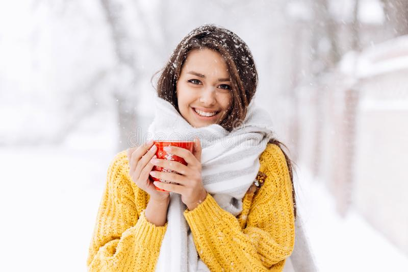 Smiling dark-haired girl in a yellow sweater, jeans and a white scarf standing with a red mug on a snowy street on a royalty free stock images