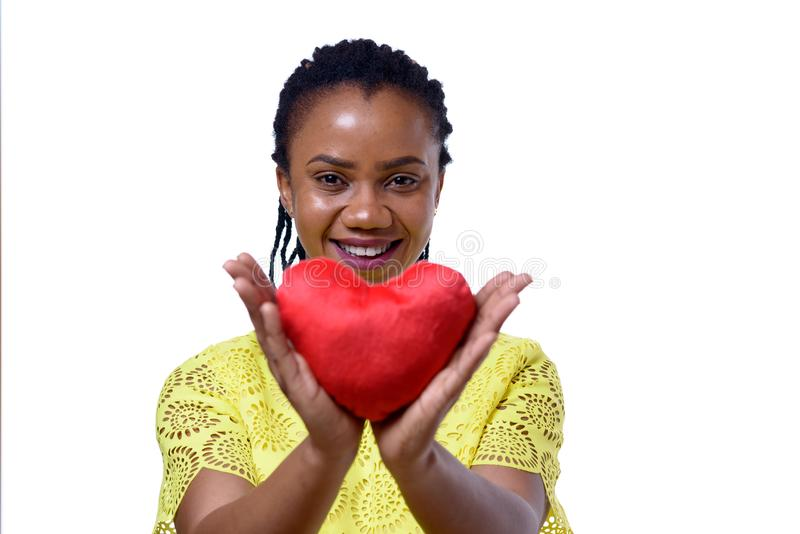 Smiling dark-skinned woman holding red heart. Portrait of smiling dark-skinned woman holding red heart, close up view royalty free stock image