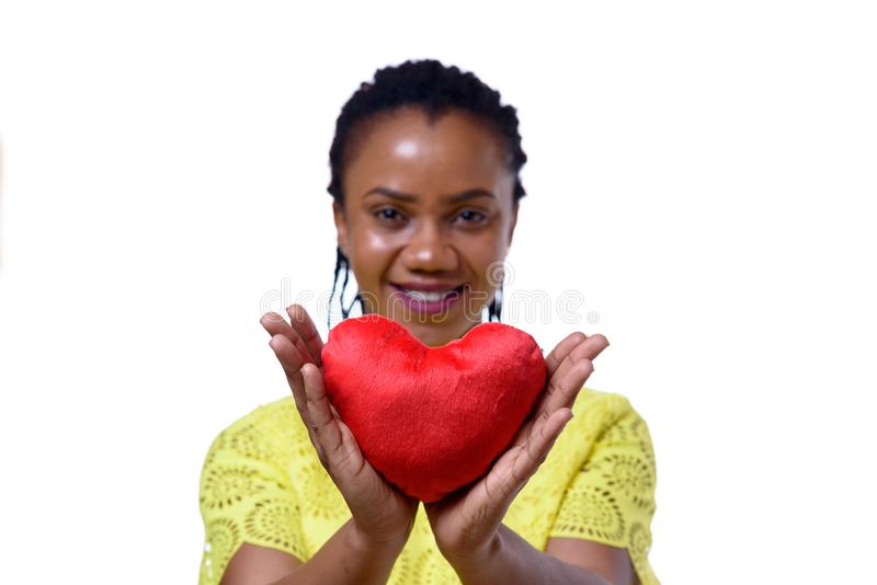 Smiling dark-skinned woman holding red heart. Portrait of smiling dark-skinned woman holding red heart against white background royalty free stock photos