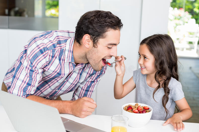 Smiling daughter feeding food to father. At home stock image