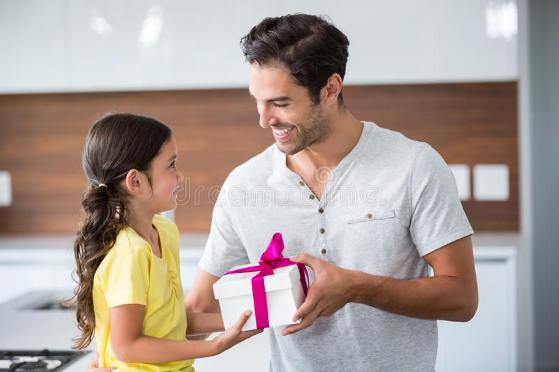 Smiling daughter giving gift box to father. At home royalty free stock photo