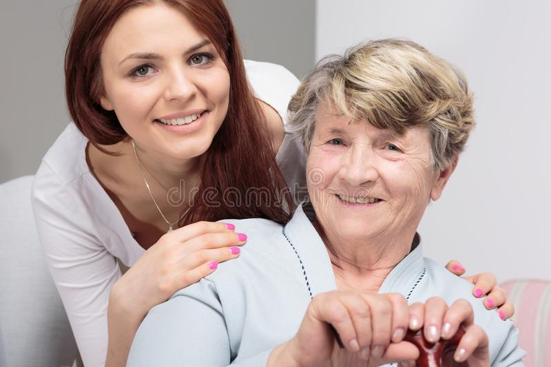 Daughter hugging happy senior mother with walking stick during meeting royalty free stock images