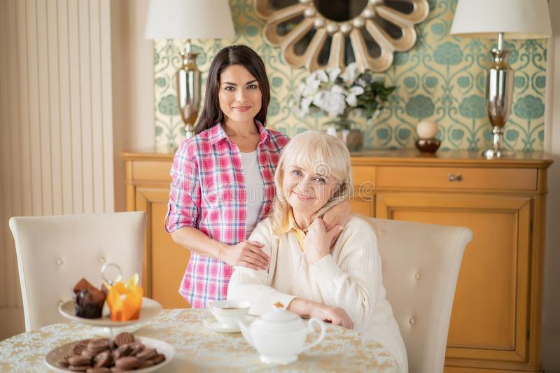 Beautiful daughter gently hugs her senior mother who sits at the table stock images