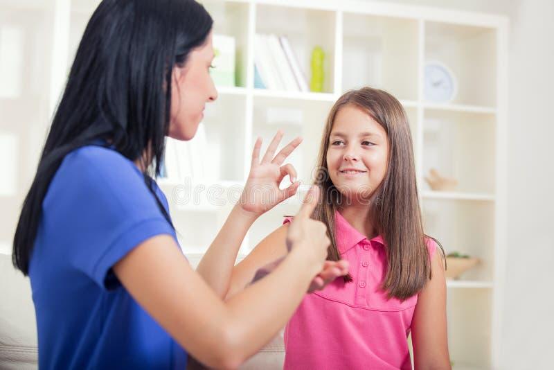 Smiling deaf girl learning sign language stock images