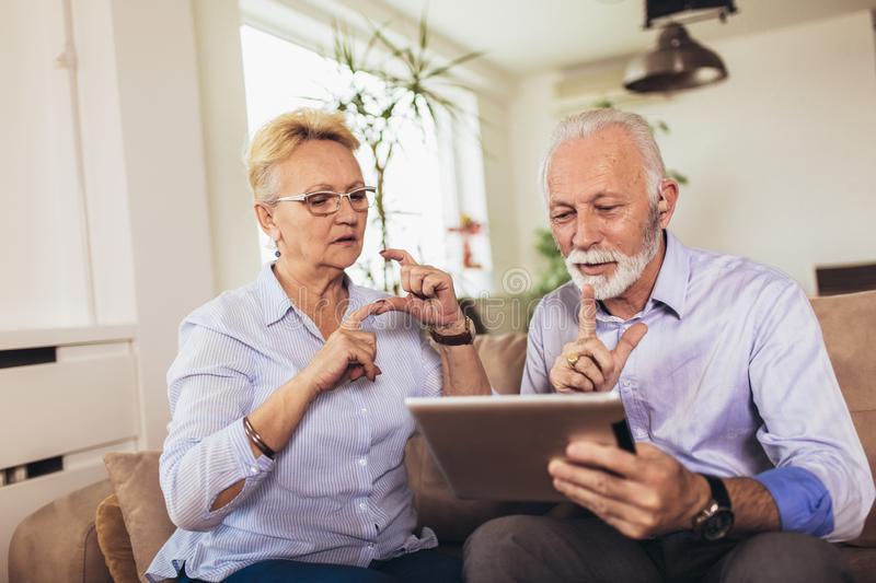 Deaf senior couple talking using sign language on the digital tablet`s cam stock photo