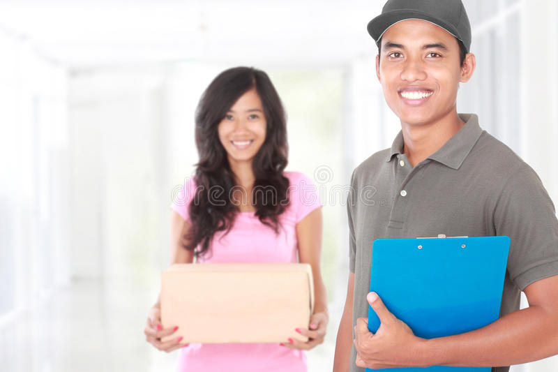 Smiling delivery guy sending package royalty free stock images