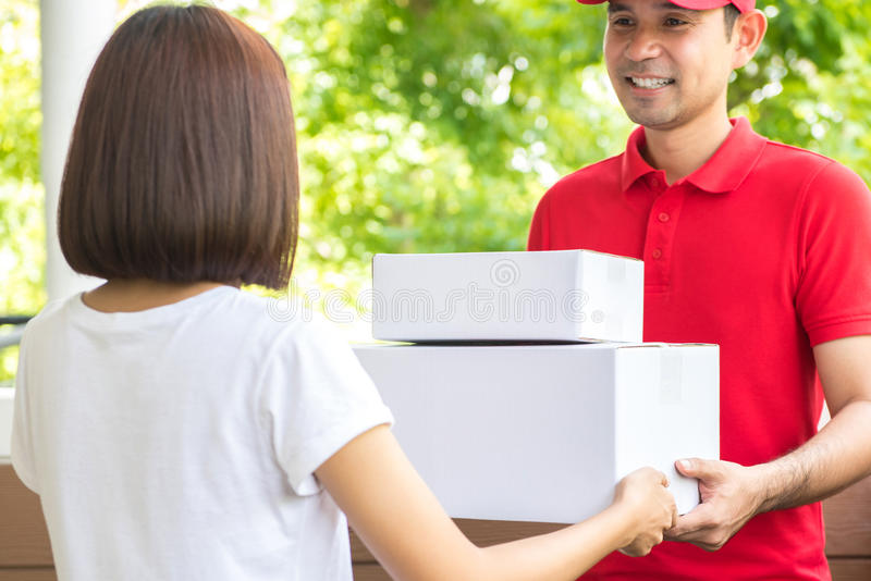 Smiling delivery man delivering parcels to a woman stock image