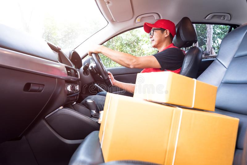 Smiling delivery man driving working deliver parcel boxes. Shipping concept royalty free stock image