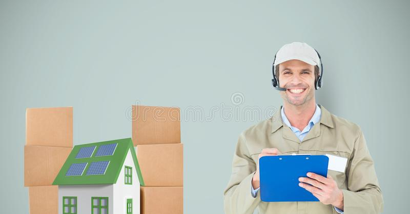 Smiling delivery man holding clipboard by house and parcels stock photos