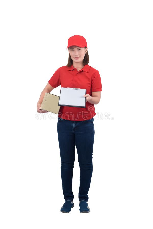 Smiling delivery woman in red uniform giving parcel boxes and clipboard, isolated on white background stock photo