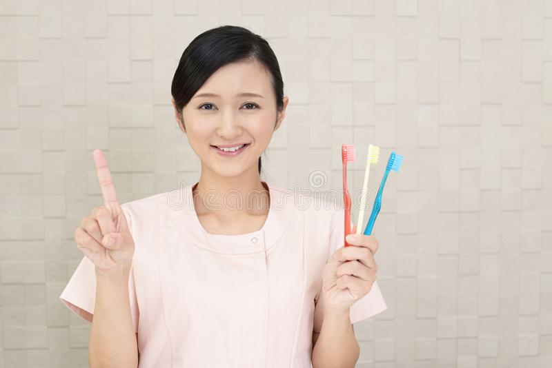 Smiling dental hygienist. With toothbrushes stock images