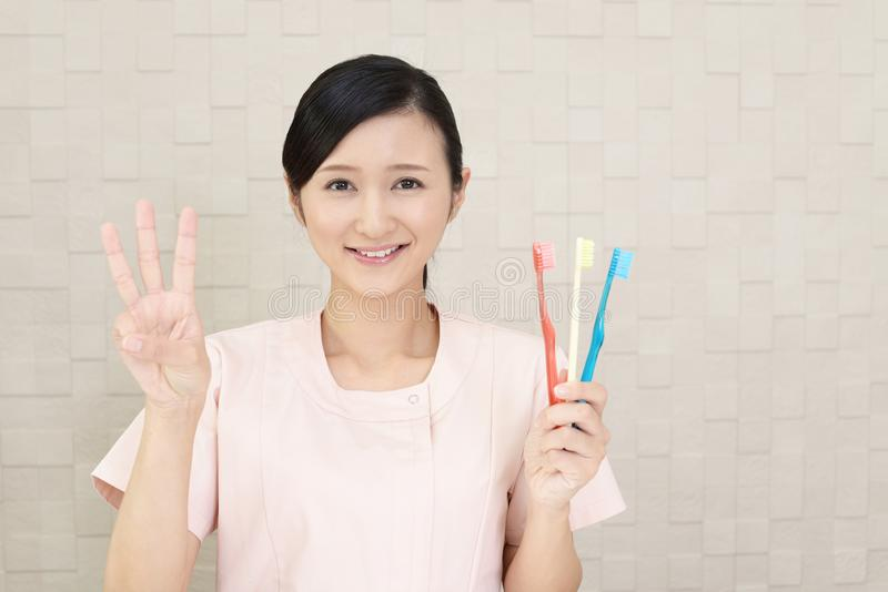 Smiling dental hygienist. With toothbrushes royalty free stock photos