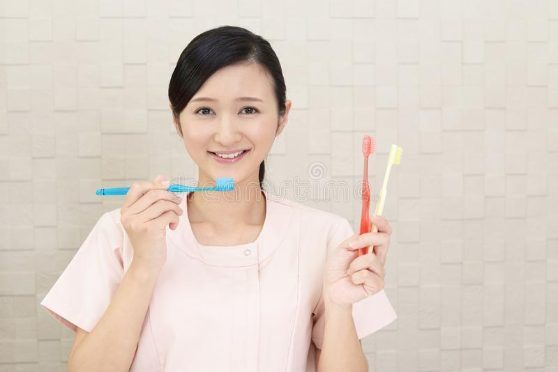 Smiling dental hygienist. With toothbrushes royalty free stock photo