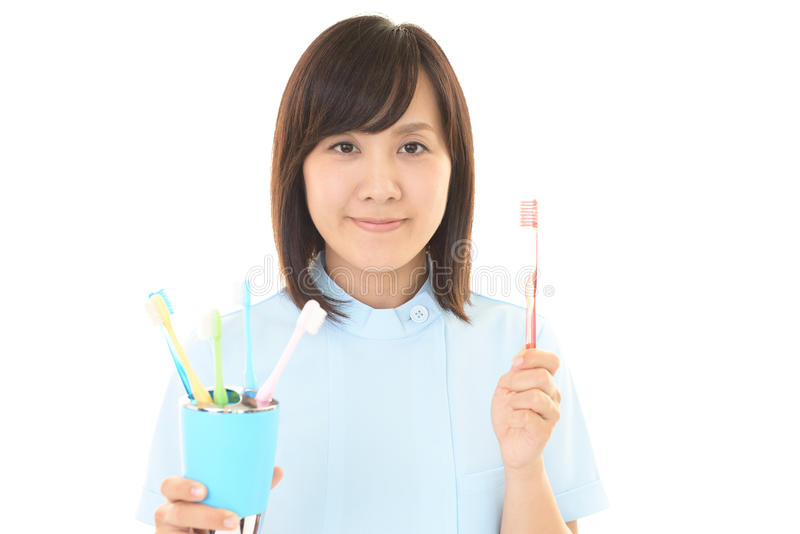 Smiling dental hygienist. With toothbrush royalty free stock image