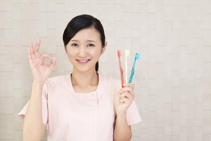 Smiling dental hygienist. With toothbrushes stock image
