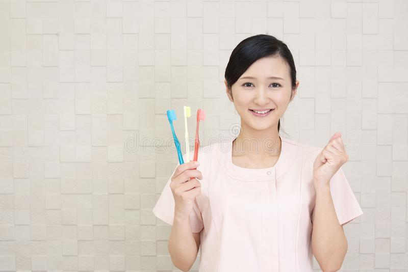 Smiling dental hygienist. With toothbrushes stock photo