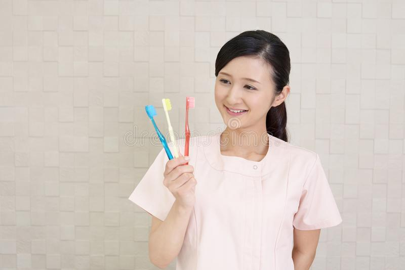 Smiling dental hygienist. With toothbrushes stock photos