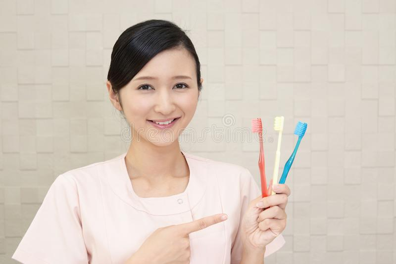 Smiling dental hygienist. With toothbrushes stock photography