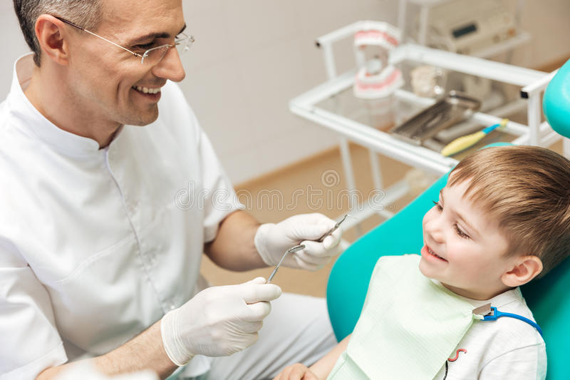 Smiling dentist doing dental treatment to little boy stock photography