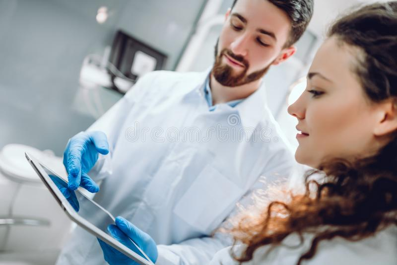 Smiling dentist and female patient looking at digital tablet during treatment in dental clinic. selective focus royalty free stock photo