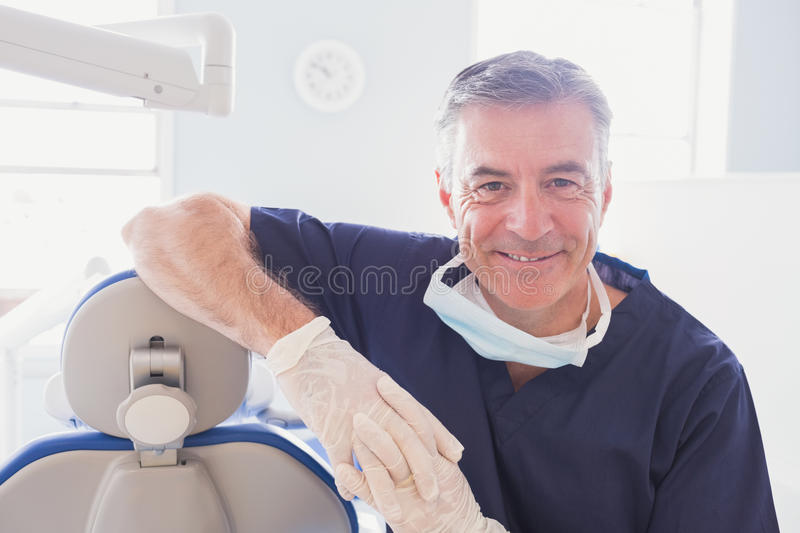 Smiling dentist leaning against dentists chair royalty free stock photography