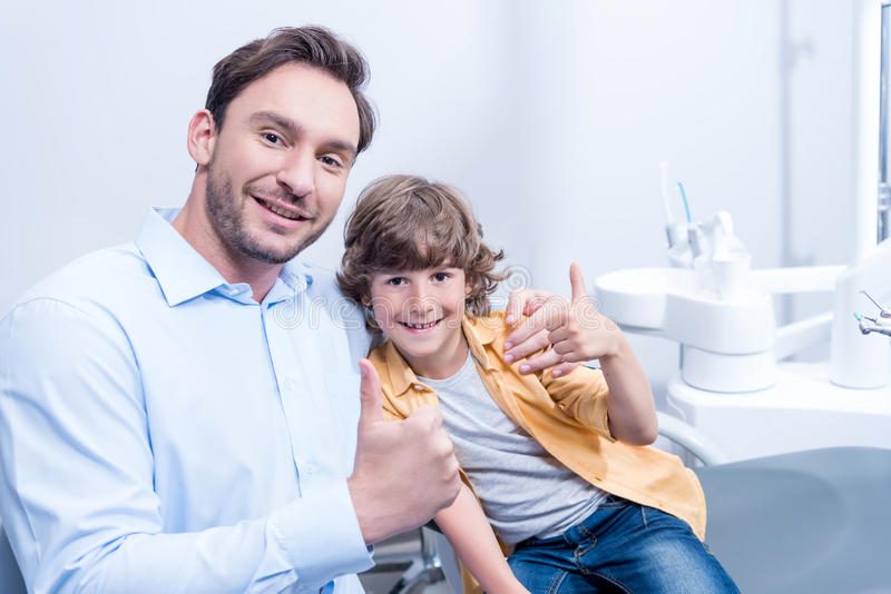 Smiling dentist and little boy showing thumbs up in dental clinic stock photography