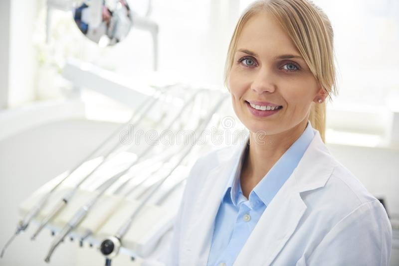 Smiling dentist in medical uniform in dentist`s clinic royalty free stock photos