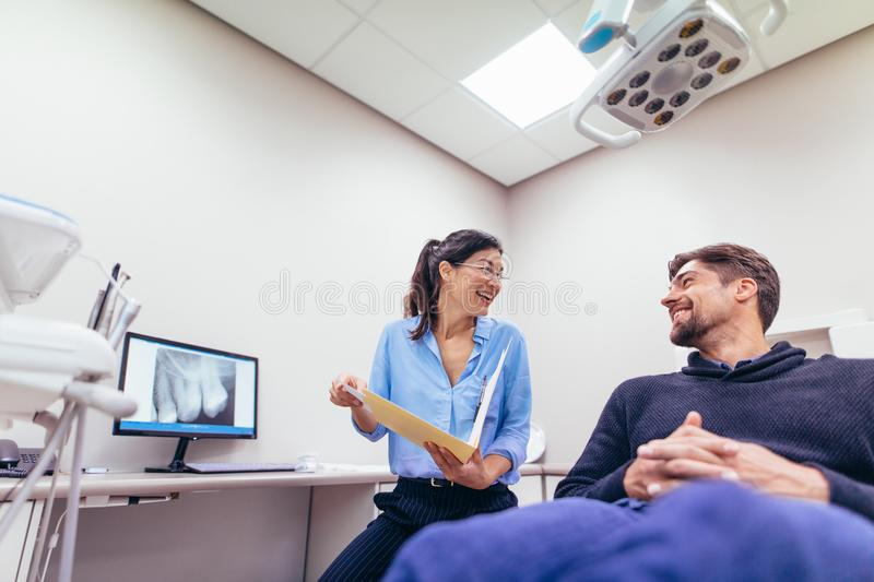 Smiling dentist and patient at dental clinic stock photo