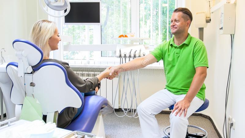 Smiling male dentist shaking hands with his patient after teeth treatment stock photos