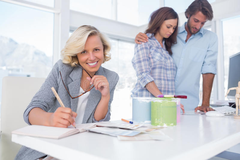 Smiling designer with a couple in her office stock photo Choosing an interior designer