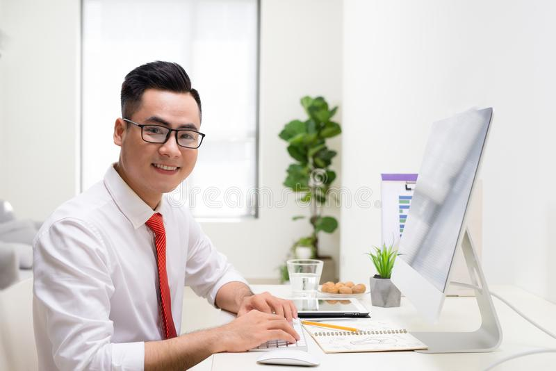 Smiling designer working at his desk in modern office stock images