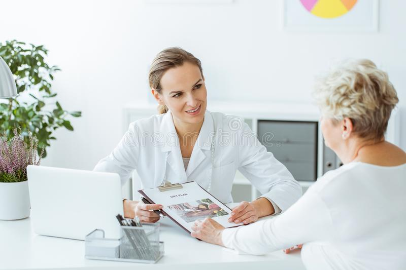 Smiling dietitian holding diet plan. Smiling dietitian holding a diet plan during consultation with patient in the office with laptop on desk stock images