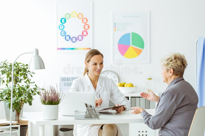 Smiling dietitian and patient. Smiling dietitian in uniform during consultation with a patient in bright office with posters royalty free stock photos