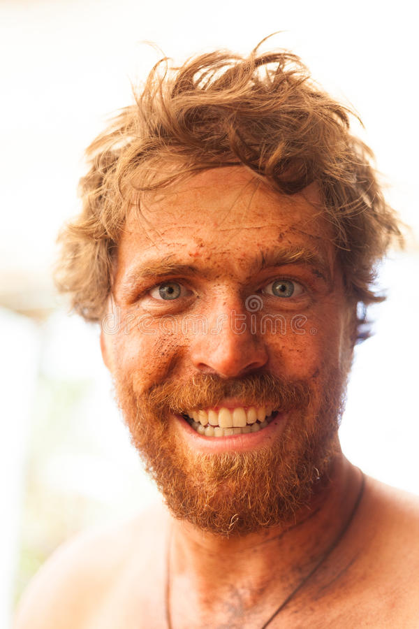 Smiling dirty ginger caveman with big beard and filth all over is face. stock photos