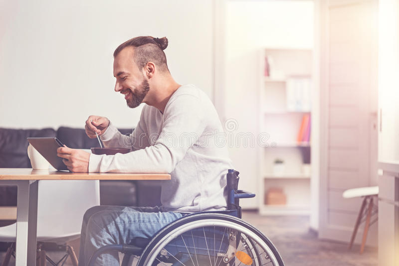 Smiling disabled male person eating soup royalty free stock photography