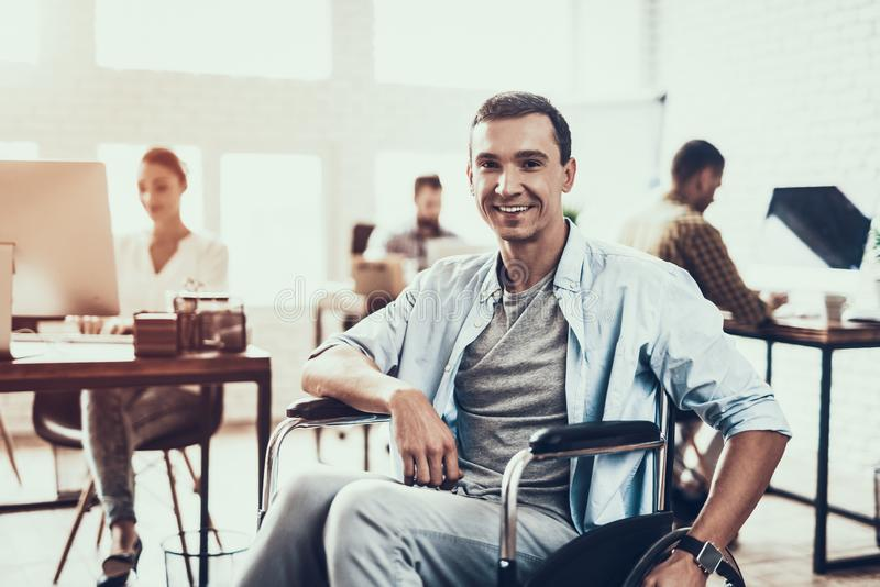 Smiling Disabled Man on Wheelchair in Office. royalty free stock photo