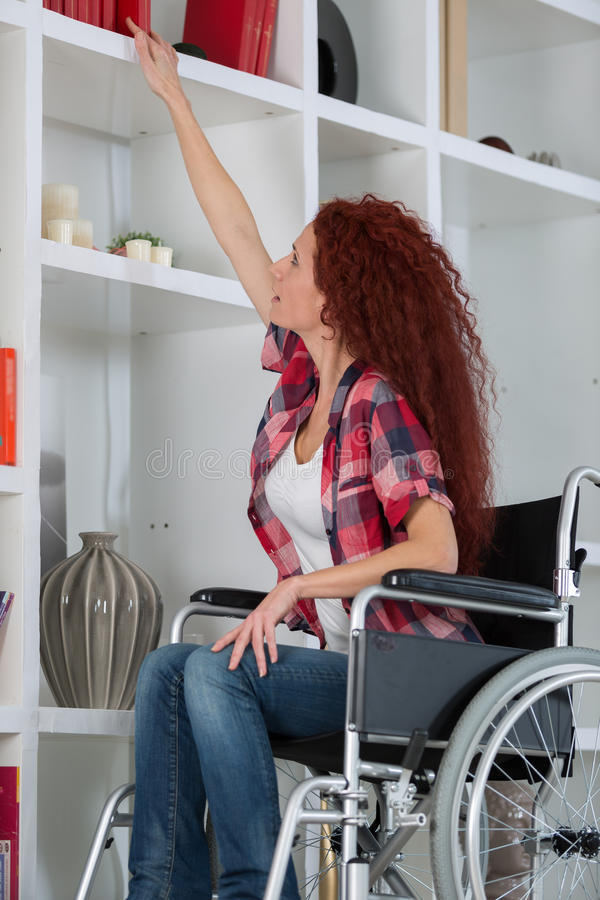 Smiling disabled student in library picking book at university stock photo