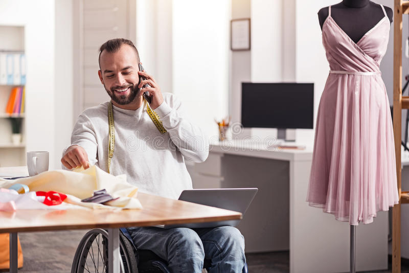 Smiling disabled tailor sharing his ideas with a friend. You might like this dress. Positive attractive attentive guy calling his friend talking about new royalty free stock image