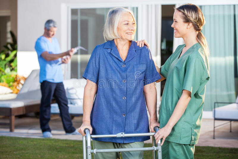 Smiling Disabled Woman And Nurse Looking At Each. Smiling disabled senior women and nurse looking at each other in lawn at nursing home stock photos